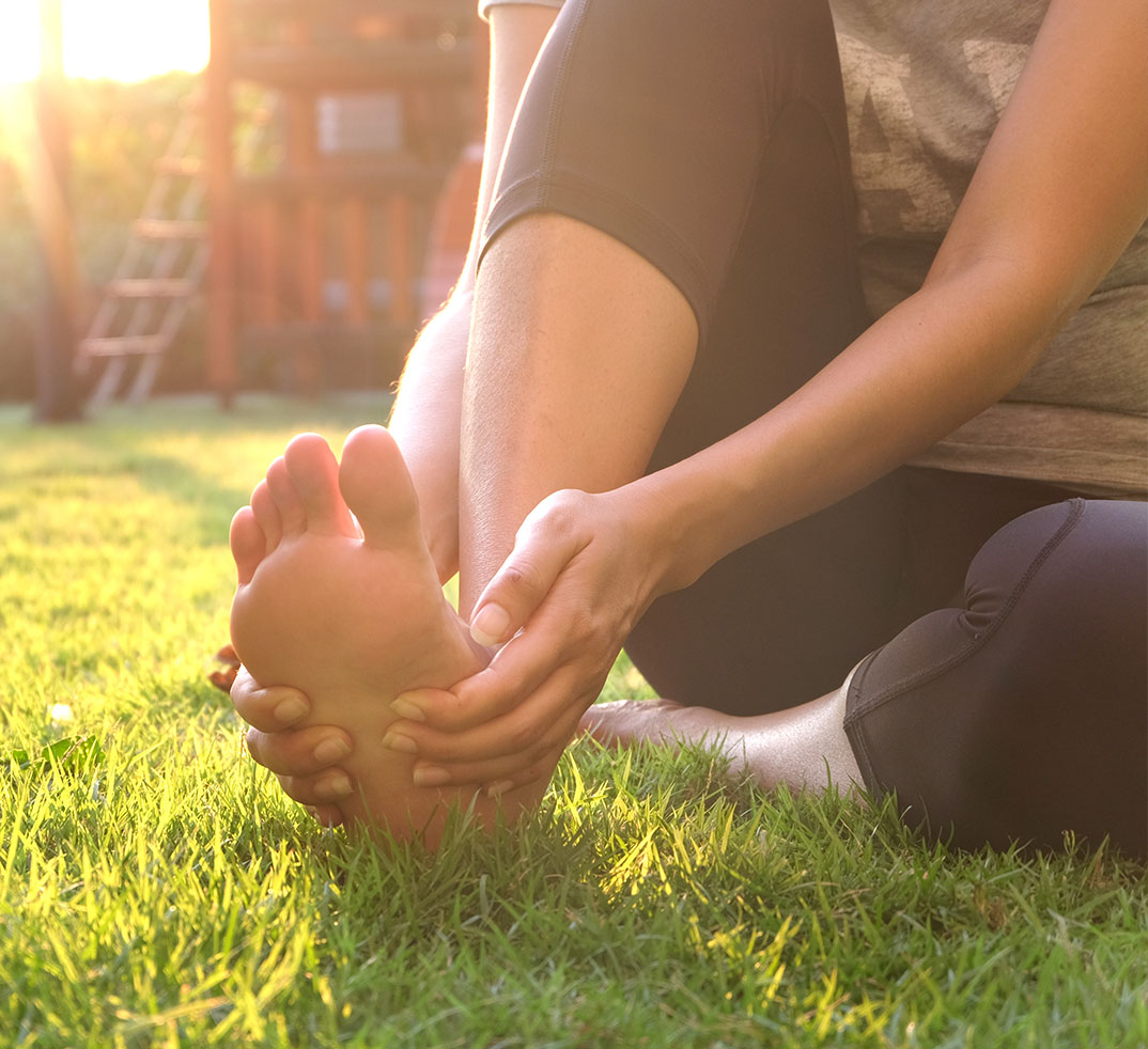 woman-rubbbing-painful-foot-on-grass